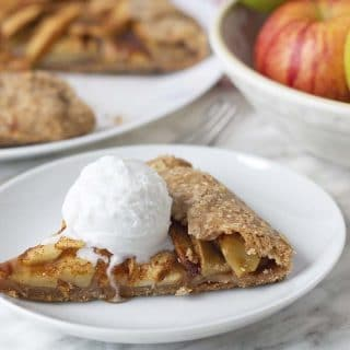 A slice of gluten free apple galette on a white plate with a scoop of coconut ice cream on top.