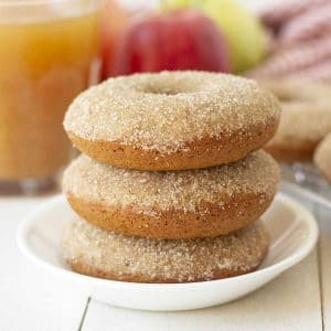 Picture of three vegan gluten-free apple cider donuts stacked on a small white plate.