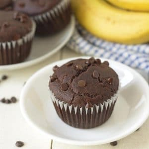 A chocolate banana muffin on a small white plate, fresh bananas and more muffins are in the background.