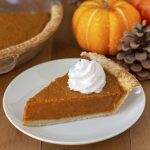 A slice of pumpkin pie on a white plate, pie has whipped cream on top, small pumpkins and pinecones are in the background.