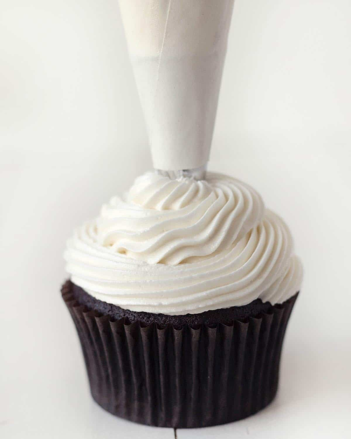 Peppermint frosting being piped onto a cupcake using a cream coloured piping bag.