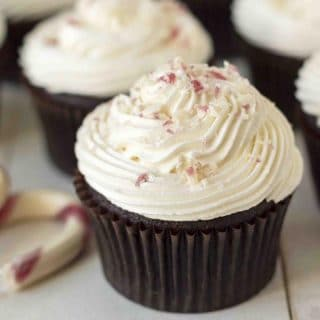 A close up shot of a freshly baked and frosted vegan peppermint chocolate cupcake sitting on a white table.