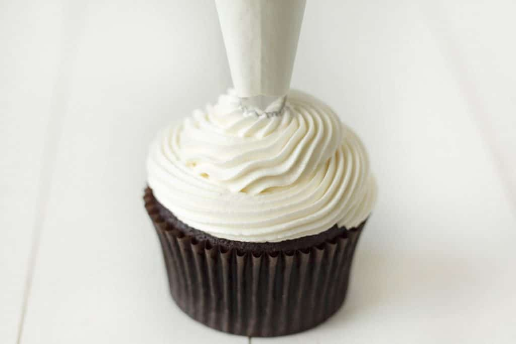 Image shows peppermint buttercream being piped onto a chocolate mint cupcake.