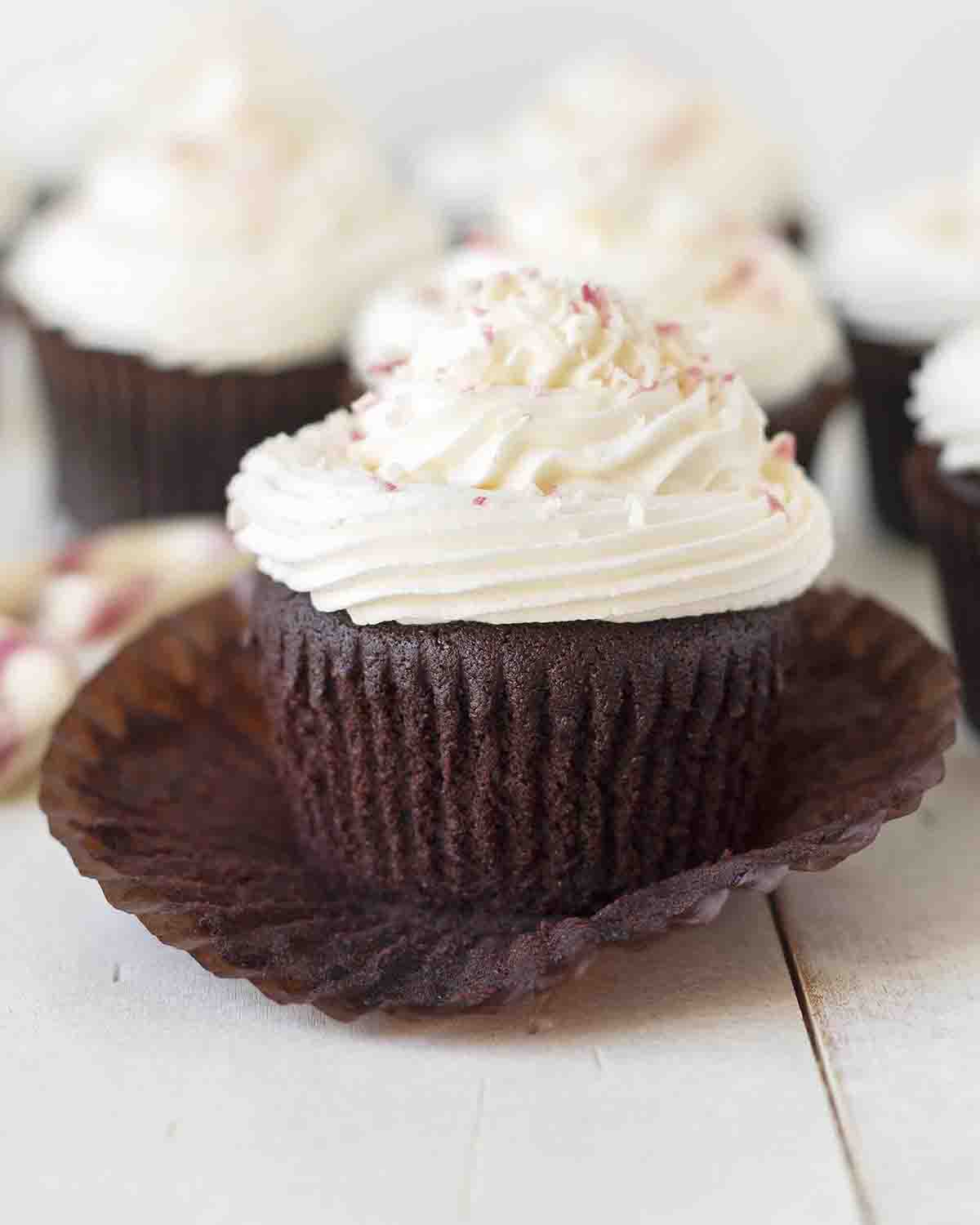 A dark chocolate mint cupcake sitting on a white table with its wrapper peeled back.