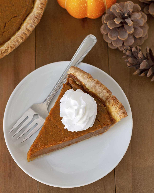 Overhead shot of a slice of vegan pumpkin pie, pie is on a white plate.