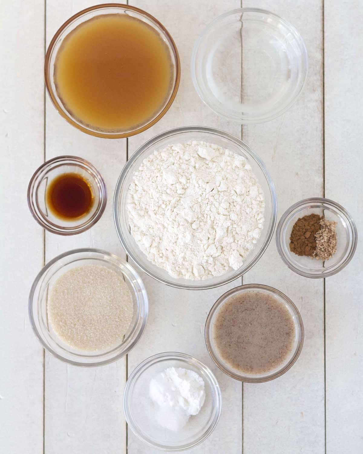 Image showing all the ingredients needed to make baked gluten-free apple cider donuts, all ingredients are in separate bowls.