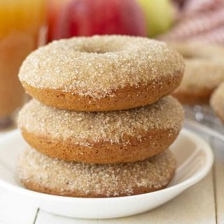 Picture of three vegan apple cider donuts stacked on a white plate.