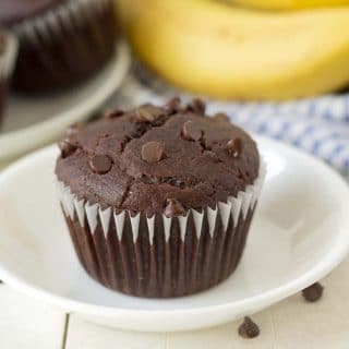 Close up shot of a chocolate banana muffin on a white plate.