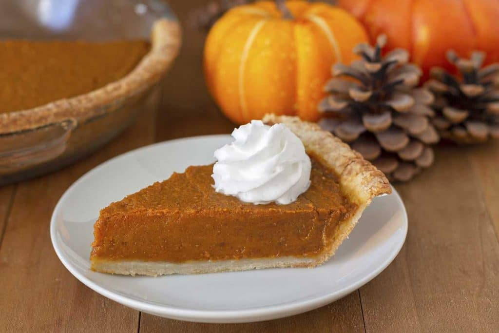 A slice of pumpkin pie on a white plate, small pumpkins, pinecones, and the rest of the pie are in the background.