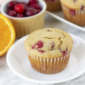 A cranberry muffin on a small white plate.