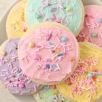 An overhead shot of colourful buttercream frosted sugar cookies with sprinkles on a plate.