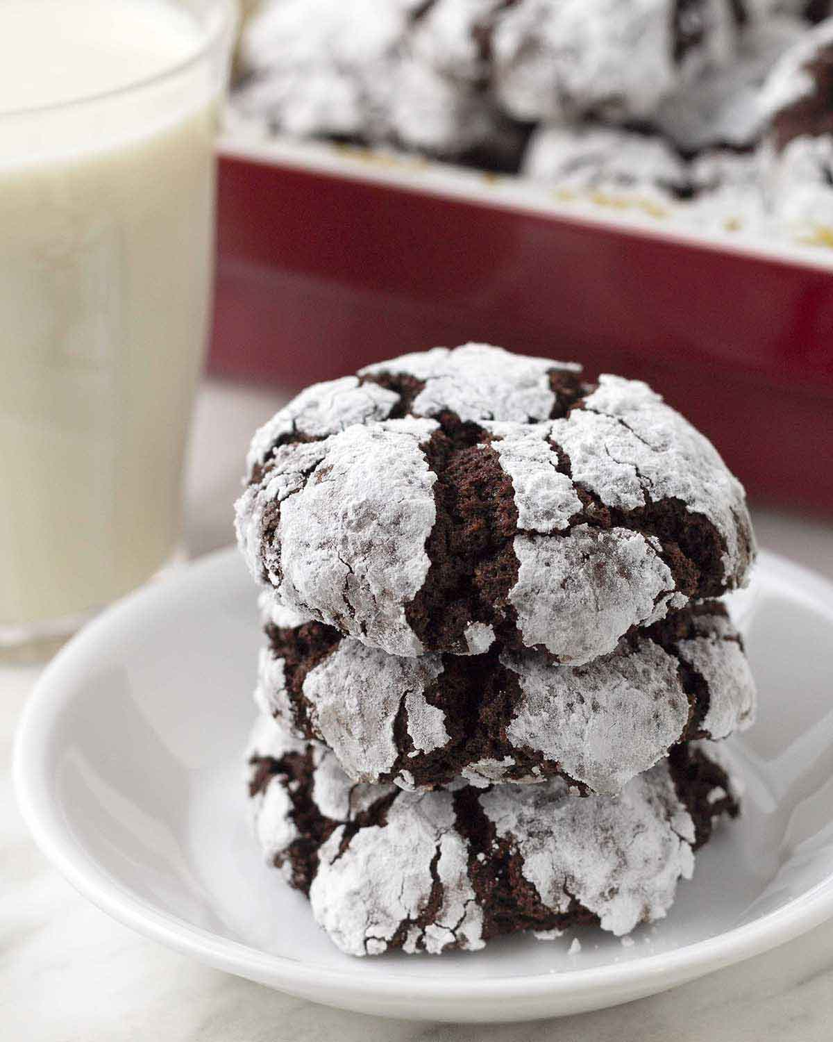 Gluten-free chocolate crackle cookies on a small white plate, more cookies and a glass of milk sit behind the plate.
