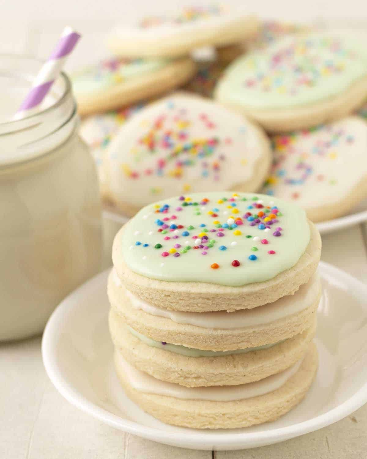 A stack of four vegan gluten free sugar cookies on a small white plate a glass of milk and more cookies sits behind.