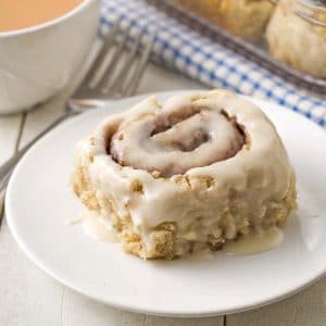 Image shows a dairy-free, egg-free cinnamon roll on plate, a cup of tea and more rolls sits behind the plate.