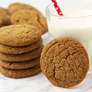 A stack of vegan molasses cookies on a table, one cookie is leaning against a glass of milk, a plate of cookies sits behind.