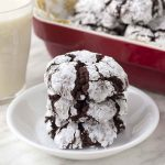 A stack of chocolate crinkle cookies on a small white plate.