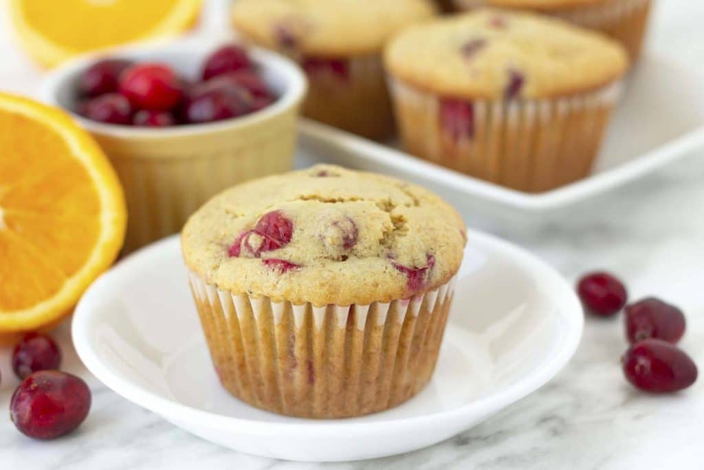 An orange cranberry muffin on a small plate, fresh cranberries are on both sides of the plate.