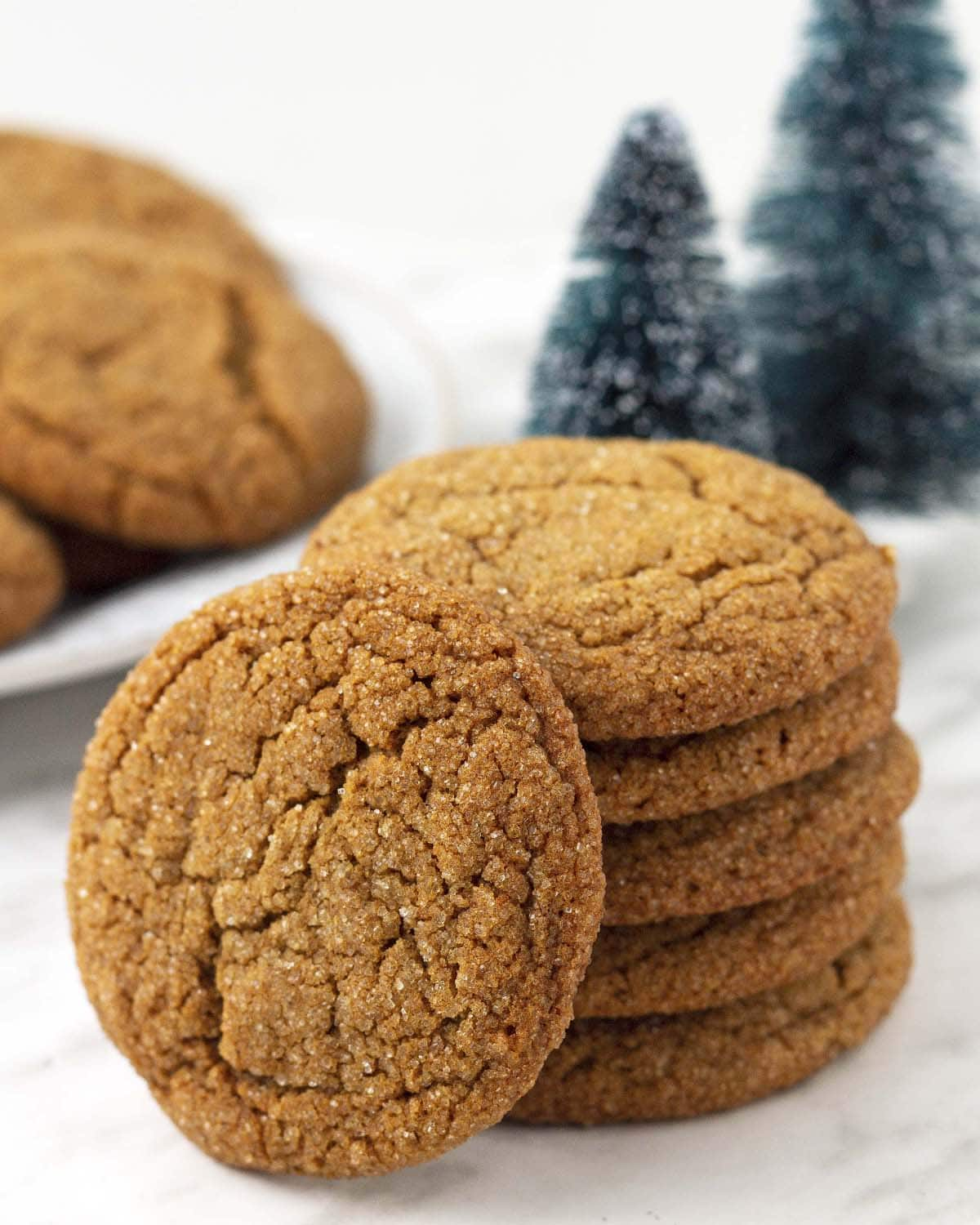 Six gluten free dairy free ginger molasses cookies stacked on a table, one cookie is leaning against the stack.