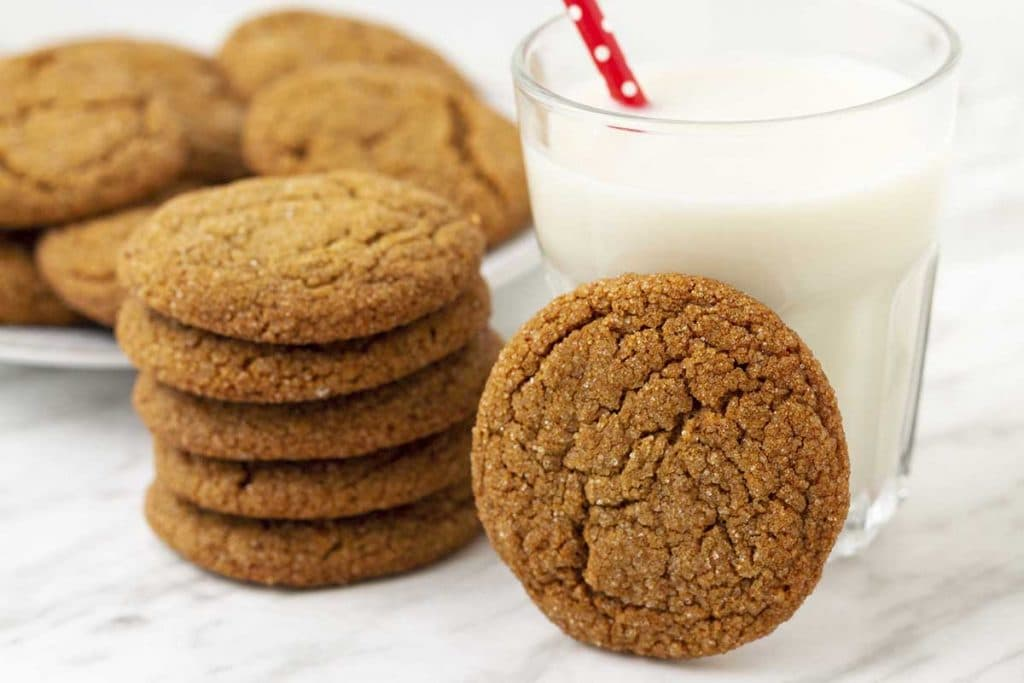 Egg free molasses cookies stacked on a table, one is leaning against a glass of almond milk, a plate of cookies sits behind.
