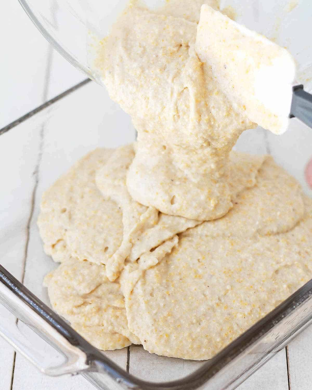 Gluten-free cornbread batter bring poured into a glass baking dish.