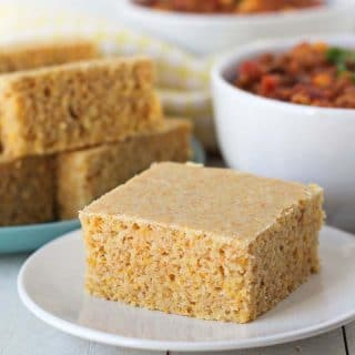 A square piece of cornbread on a white plate, two bowls of chilli sit in the background as well as a plate of more cornbread.