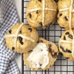 Overhead shot of hot cross buns on a cooling rack, one bun is split and is buttered.