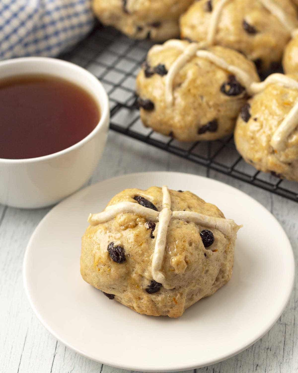 A hot cross bun on a white plate, more buns sit behind on a cooling rack, a cup of tea sits to the left of the plate.