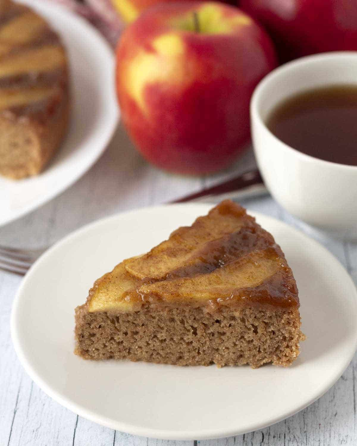 A slice of vegan gluten-free apple upside down cake on a small white plate.