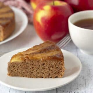 A piece of gluten-free apple upside down cake on a small white plate, fresh apples sit behind the plate.