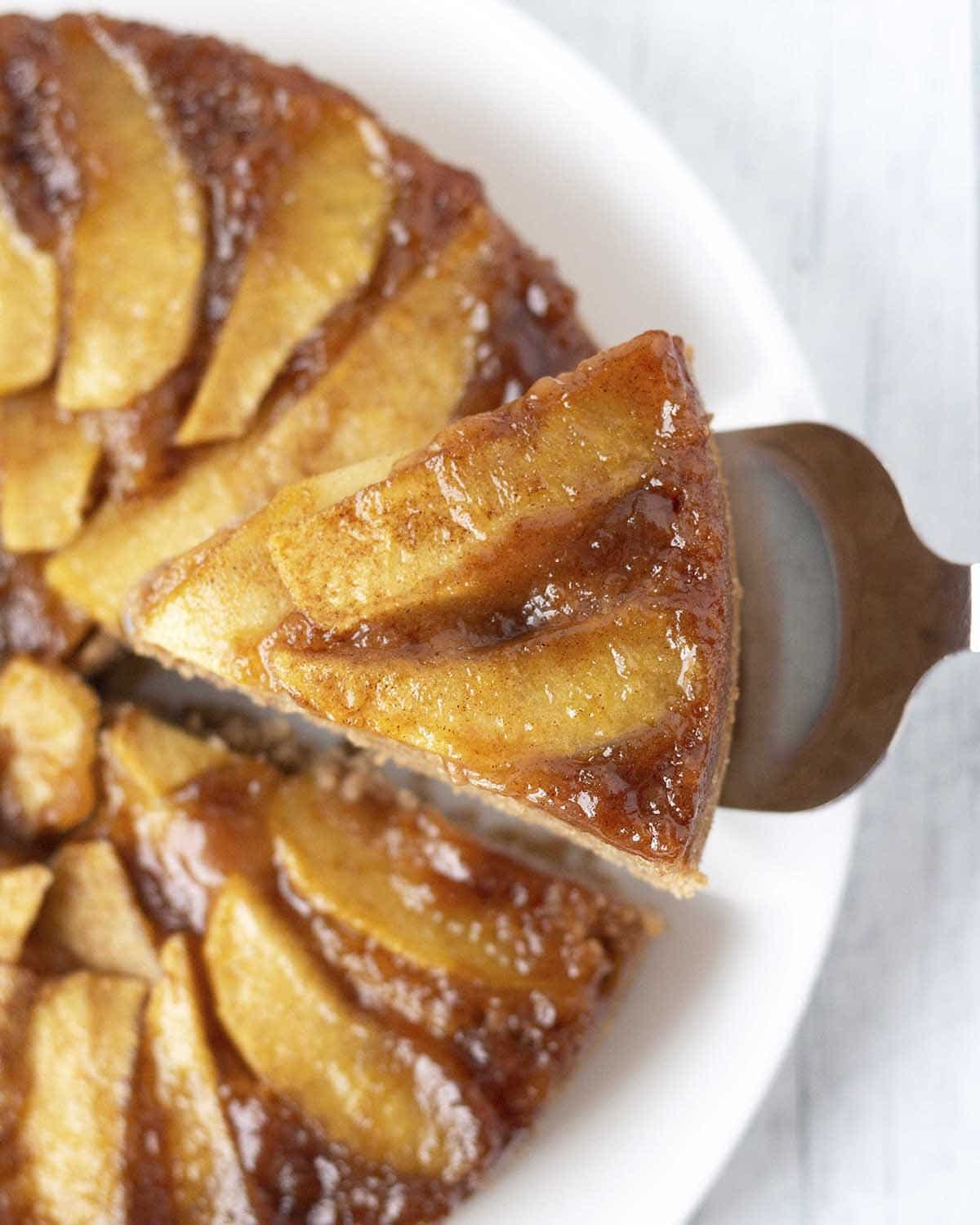 Overhead shot of a slice of vegan gluten-free apple upside down cake being held up over the cake with a serving spatula.