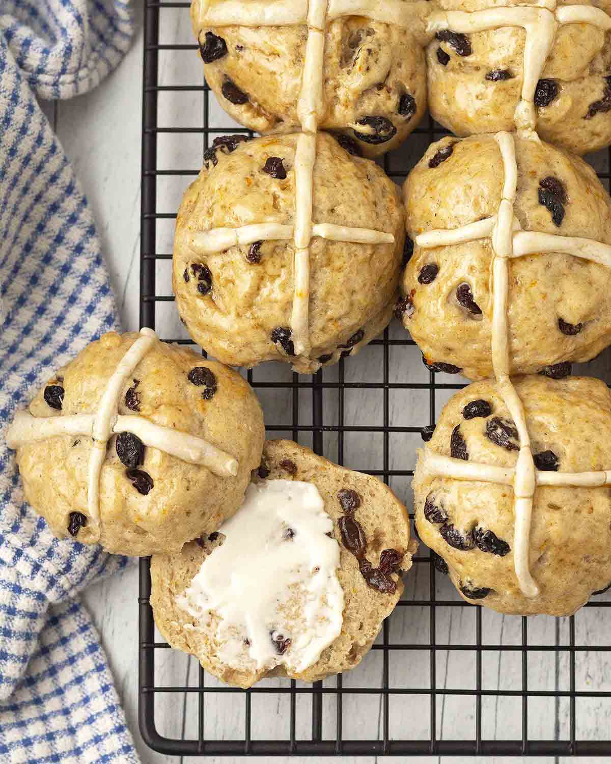 An overhead shot of hot cross buns on a cooling rack, one bun is split and has butter spread on one half.