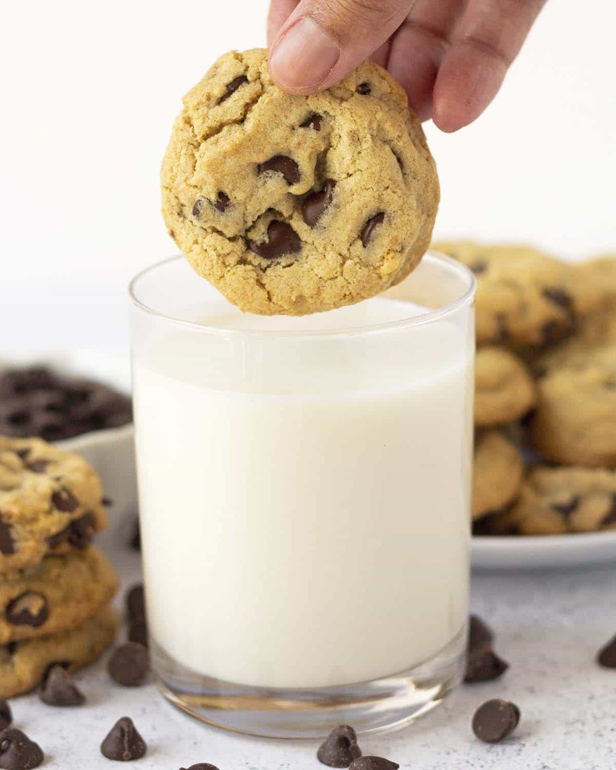 A hand holding a gluten-free chocolate chip cookie above a glass of almond milk.
