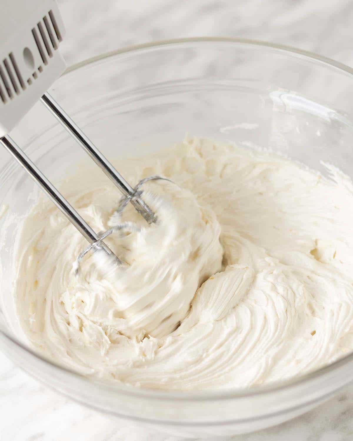 Image shows an electric beater whipping vegan lemon frosting in a glass bowl.