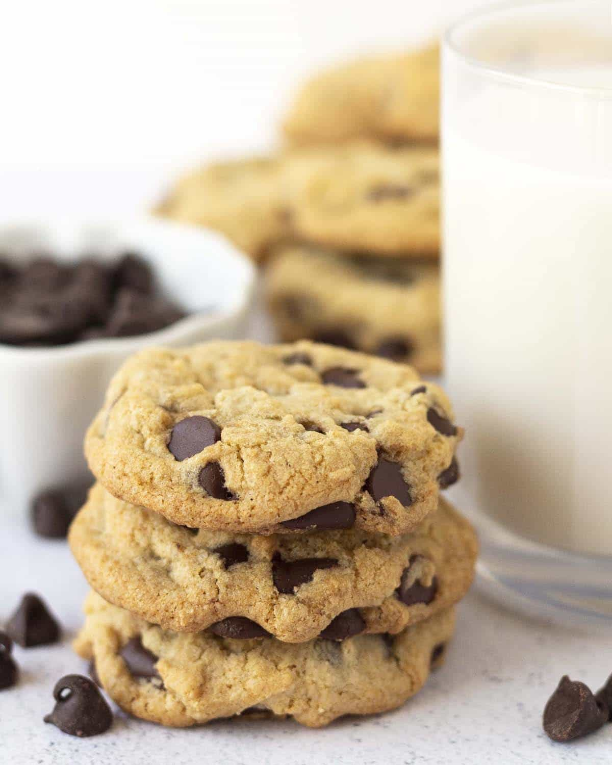 A stack of three vegan gluten-free chocolate chip cookies sitting in front of a glass of almond milk.