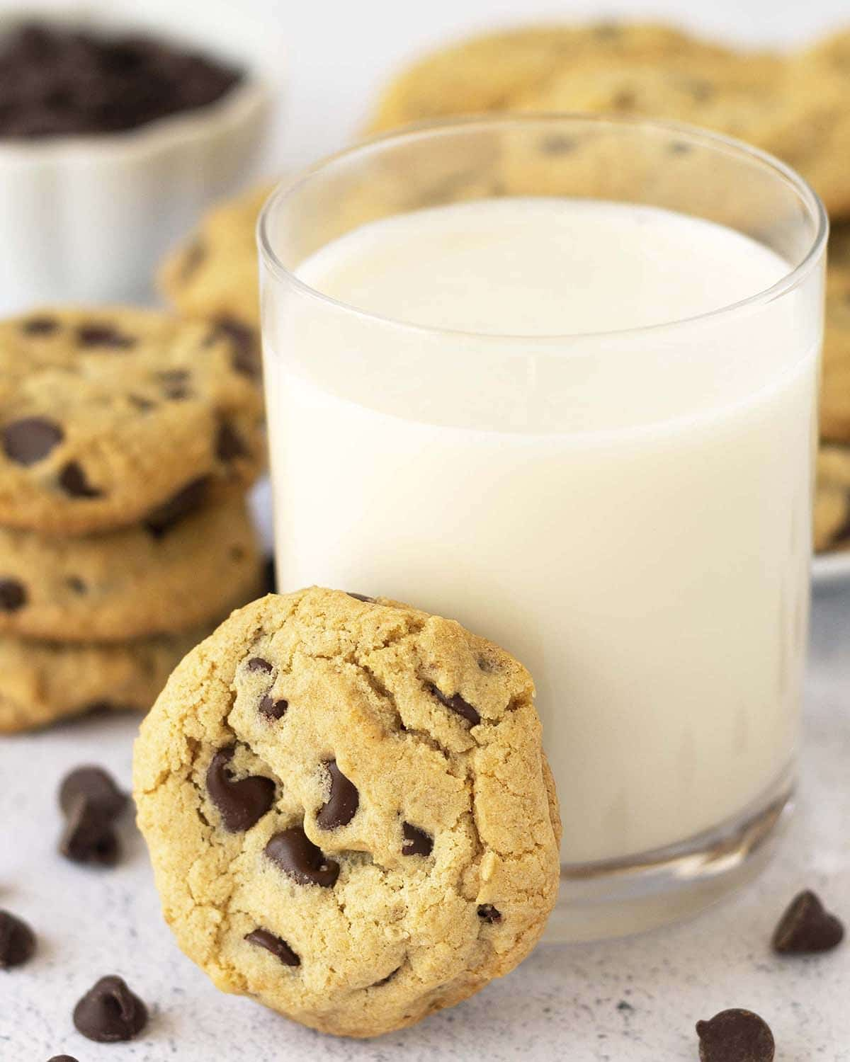 A dairy and egg free chocolate chip cookie leaning against a glass of almond milk.
