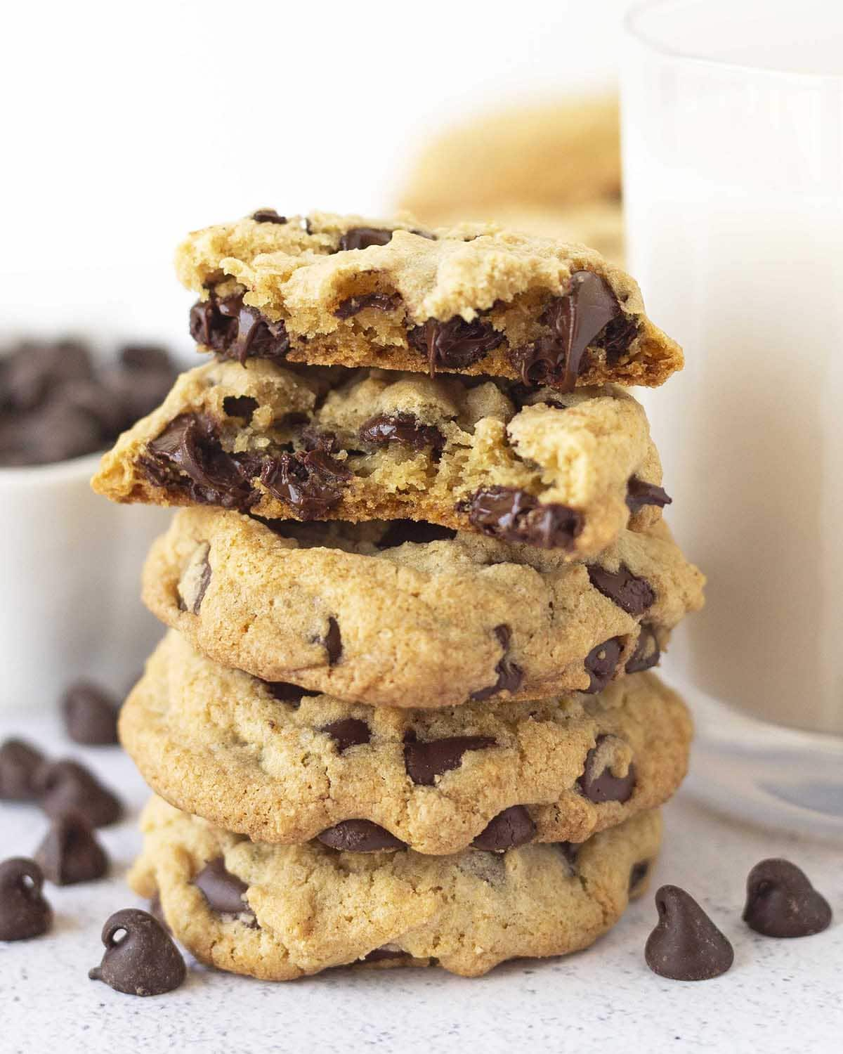 A stack of four chocolate chip cookies, the cookie on top is split in half to show the inner soft, gooey texture.
