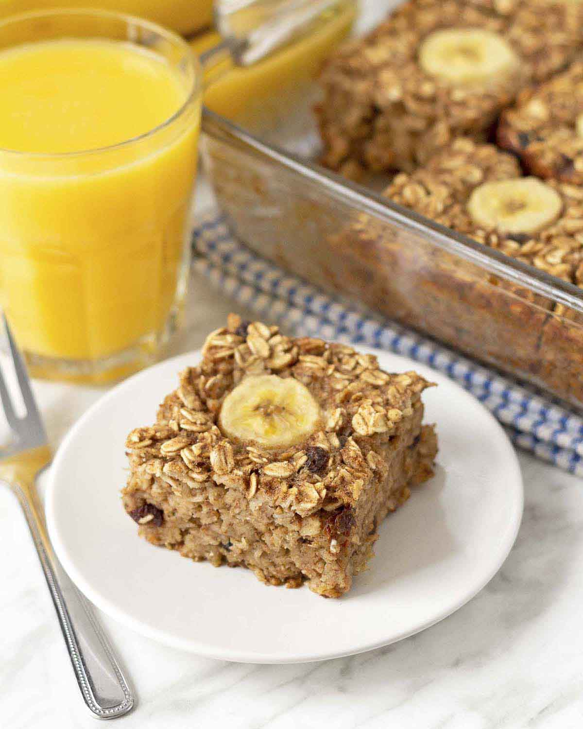 A square of banana bread baked oatmeal on a white plate, a fork sits to the left of the plate.