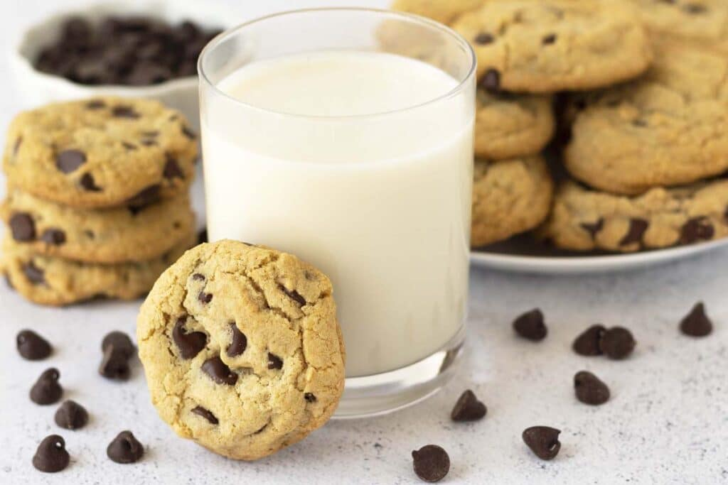 A chocolate chip cookie leaning against a glass of almond milk, more cookies sit on a plate behind the almond milk.