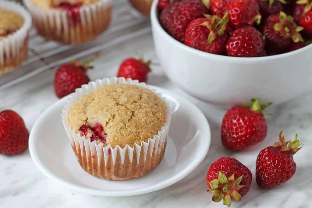 Vegan strawberry muffin on a small white plate.