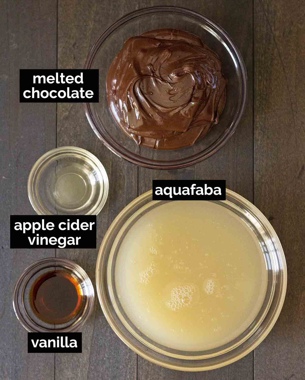 Overhead shot of the four ingredients needed to make aquafaba chocolate mousse (chocolate, aquafaba, vinegar, and vanilla).