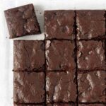 An overhead shot of a batch of eggless brownies, the brownie in the top left corner is pulled away from the rest.