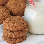 A stack of three oatmeal cookies sitting beside a glass of milk.