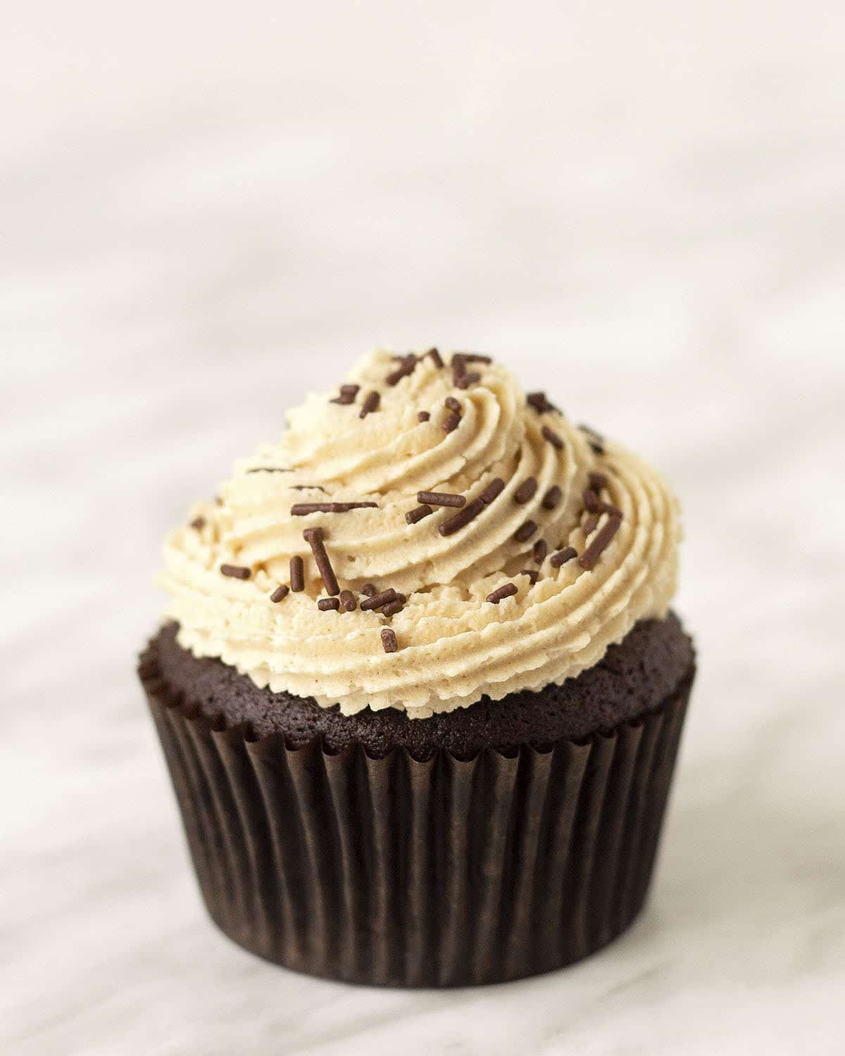 A chocolate cupcake topped with peanut butter icing and chocolate sprinkles.