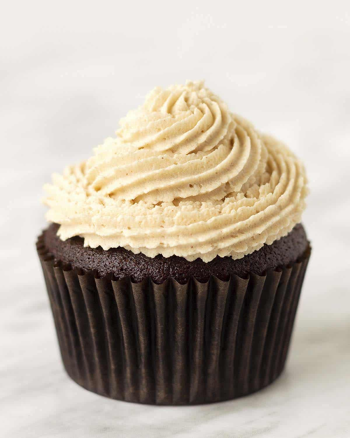 A chocolate cupcake topped with peanut butter flavoured frosting.
