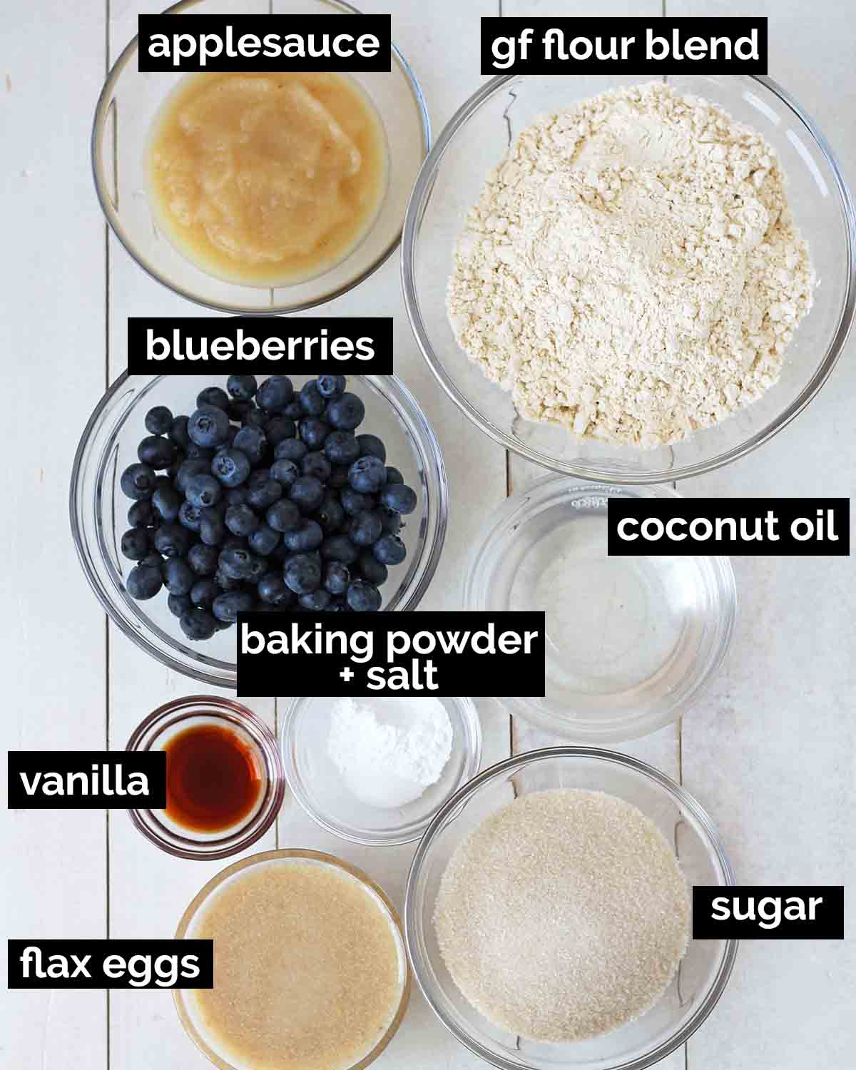 Overhead shot of the ingredients needed to make vegan gluten-free blueberry muffins. Each ingredient is labeled.