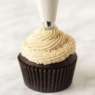 Peanut butter frosting being piped onto a cupcake with a piping bag.