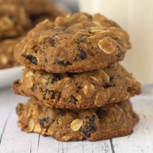 A close up shot of three oatmeal raisin cookies stacked on top of each other.