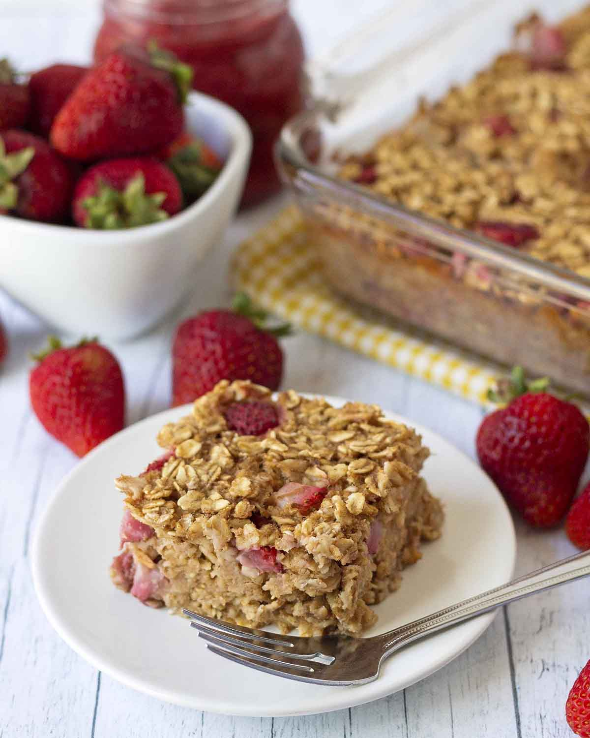 A slice of freshly baked strawberry oatmeal casserole on a plate. Fresh strawberries are around the plate.