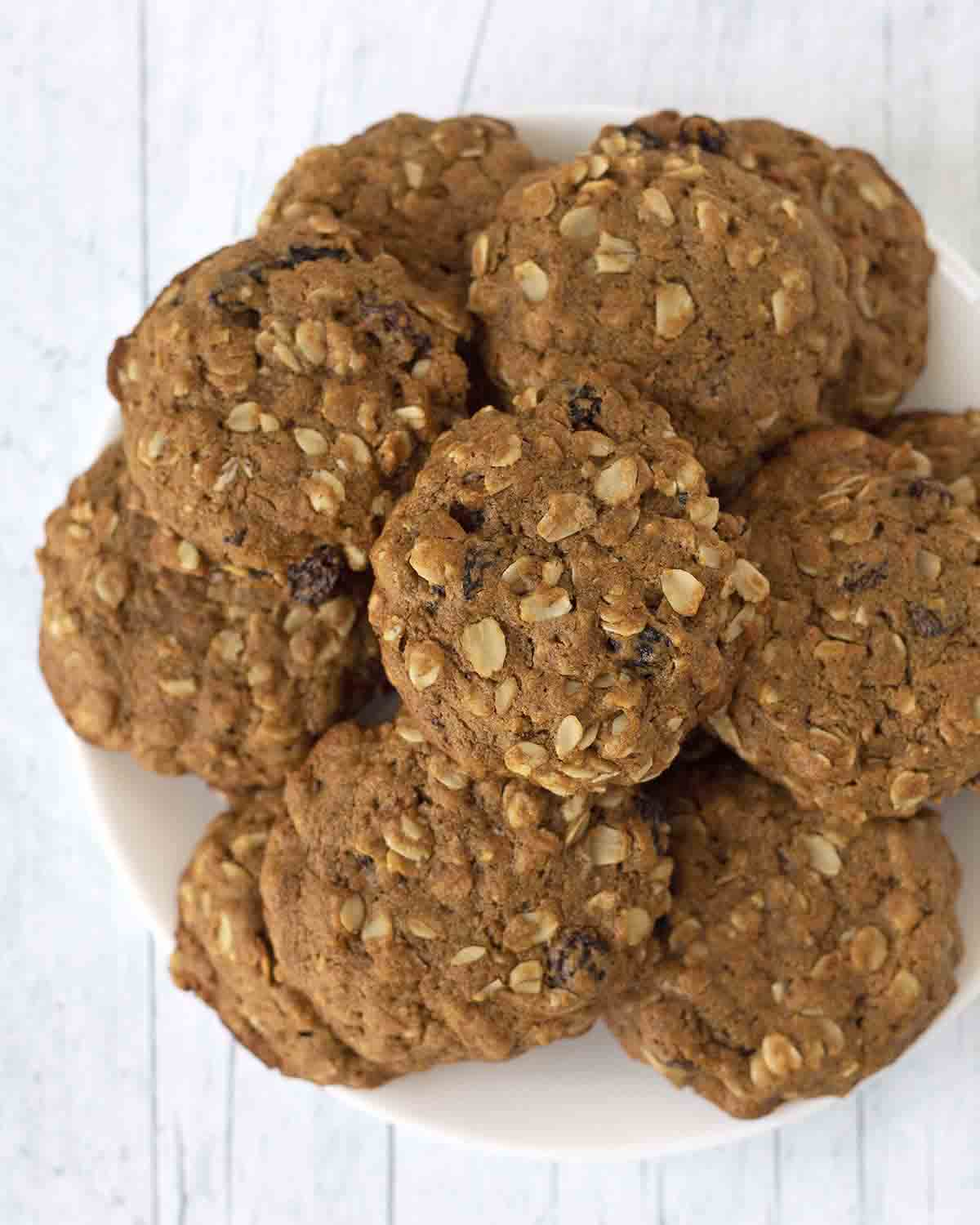 An overhead image showing a plate full of soft-baked vegan oatmeal raisin cookies.