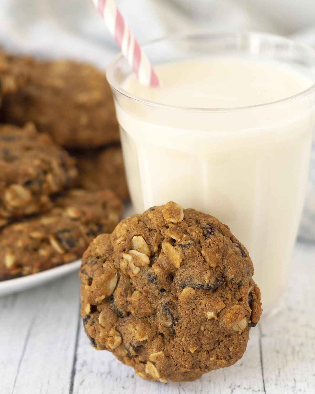 An oatmeal cookie leaning against a glass of almond milk, the glass has a pink straw in it.